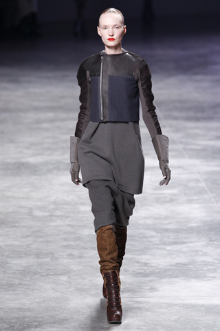 "The tunics and loose trousers tucked into boots at Rick Owens' autumn/winter 2011 collection shown at the Paris prêt-à-porter season today, suggested a slight Cossack air to me. The designer, however, was quick to clarify my interpretation; I was way off the radar, by a few millennium, at least. ""Cossack? No! I was thinking more caveman; you know, the idea of 'just throw a blanket over her'. That was my basis."" If indeed 'troglodytes' were Owens' starting point, then he has crafted a best-dressed 'Neanderthal look' which would suggest Raquel Welch in 'One Million Years B.C.' was very poorly served indeed, by the wardrobe department. This was in no way a question of 'just throwing a blanket' over anyone. The collection was a superbly crafted, proportioned and coloured blend of pieces, which started with a hood, or knitted 'snood', and progressed through a series of layers, through to wedge-soled knee-boots."